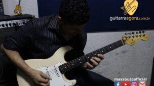 homem sentado tocando guitarra branca