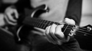 guitarrista dedilhando na guitarra