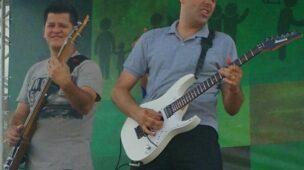 dois homens tocando guitarra em palco com gelo seco